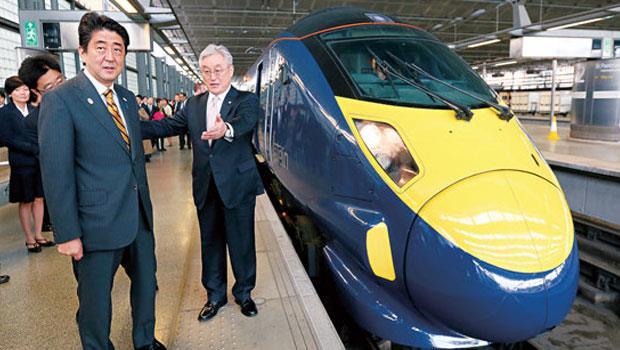 日立淡出家電領域之際,積極布局高鐵建設,把鐵路工程總部遷往英國倫敦,日相安倍(左)甚至當起首席推銷員。
