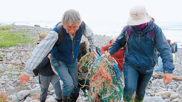 調查小組長時間觀察廢棄物,記錄溪岸人為利用及影響。