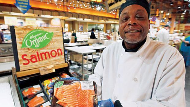 威格曼超市內設的烹調教練手捧有機養殖的帝王鮭,解說食材特色。