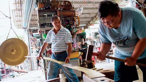 林午鐵工廠第三代傳人林浩賢(右)自小見習銅鑼製作,大學畢業後決定投身傳統技藝,並攻讀佛光大學文化資產與創意學系研究所結合家業與專長。