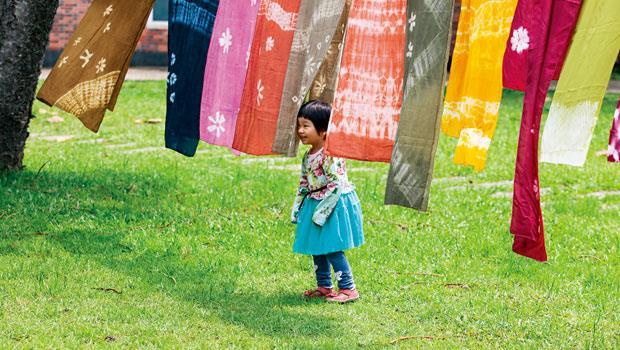 植物染花布巾掛在繩上等待風乾。在鳳林公園玩耍的小妹妹,被五顏六色的花布巾吸引而來。