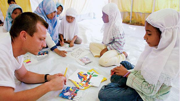 法國志工瑟瑞爾(Cyrille,左)利用假期,赴印尼鄉間教授繪畫藝術。