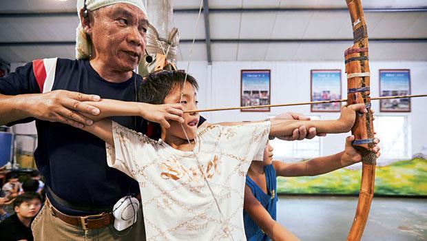 王國榮指導小朋友射箭,左手打直,右手拉弦放箭。看看他們的眼神,可預見這支箭快狠準!
