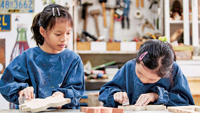 孩子專心研磨木板邊緣,留意手作細節替玩具質感加分。