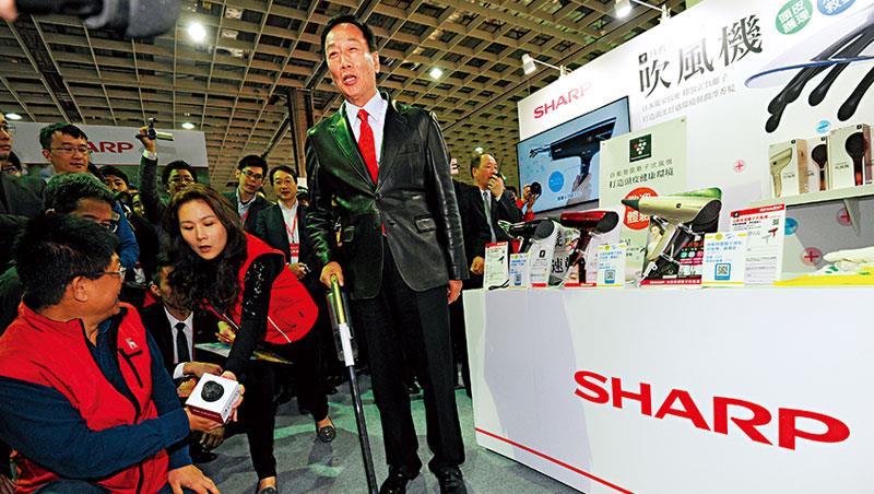 不只賣大電視,為推銷夏普產品,郭董(中)在尾牙現場當起銷售員,親自試用吸塵器。