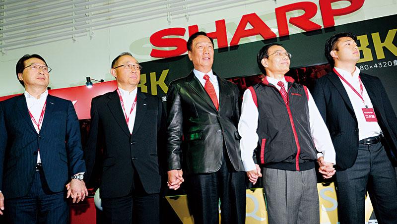今年初尾牙,郭台銘(圖中)與夏普社長戴正吳(右2)、夏普創辦人後代手牽手,站在自豪的面板前,宣示布局新技術的野心。