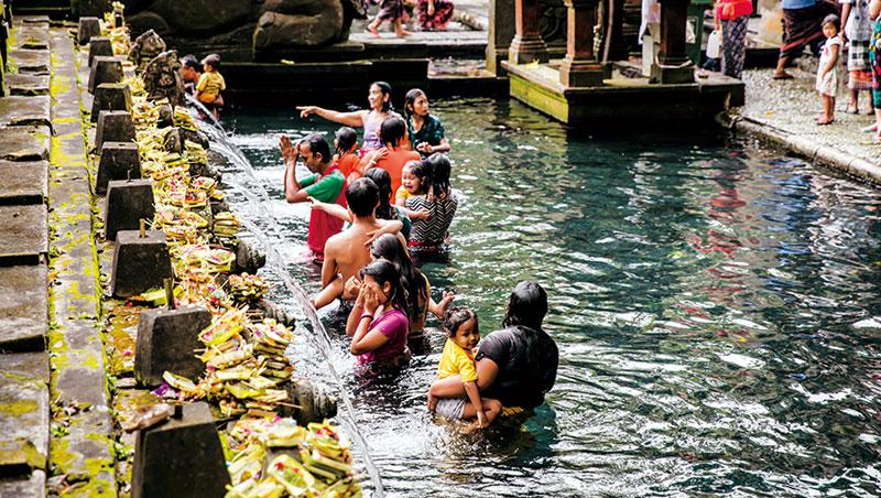 峇里島父母喜歡帶小孩來聖泉廟沐浴聖水,水柱出口處上方擺滿了獻給神明的供品。