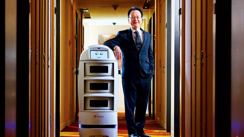 這一台看起來像吸塵器的機器人要價約新台幣 210 萬元,但有政府補助,飯店回收期從 1 年縮短為 9 個月。圖右為負責把機器人導入酒店的總經理孫禮敬。