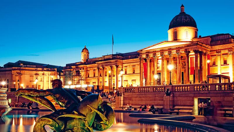 倫敦國家美術館每週五開放至晚上9點,霓虹燈映照廣場噴泉中由男人魚、海豚和鯊魚所組成的銅像。