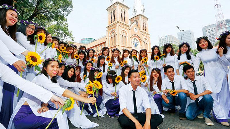 胡志明市著名景點紅教堂旁,大學生開心拍畢業照。這個十歲至二十四歲占全國四成人口的國度,近年開始廣設大學,為未來經濟轉型打下基礎。