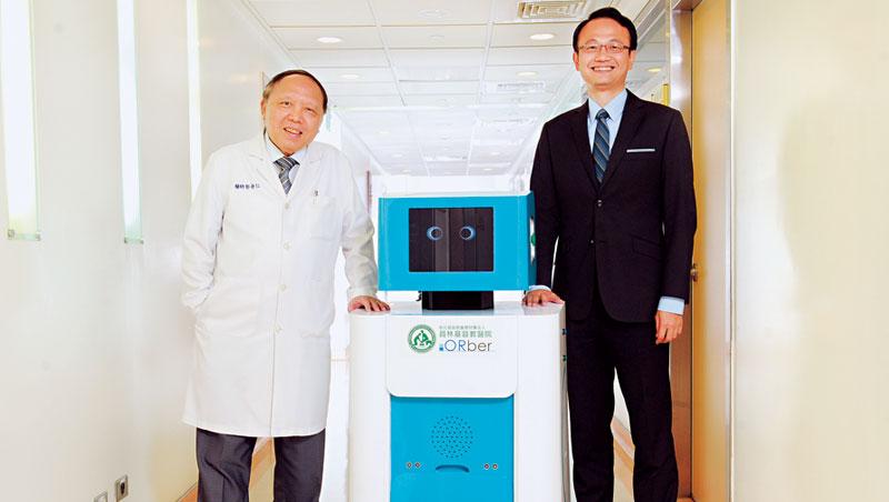 醫療機器人可負重200 公斤器械,將來還會打招呼。(左為彰基院長郭守仁,右為慧誠智醫總經理余金樹)