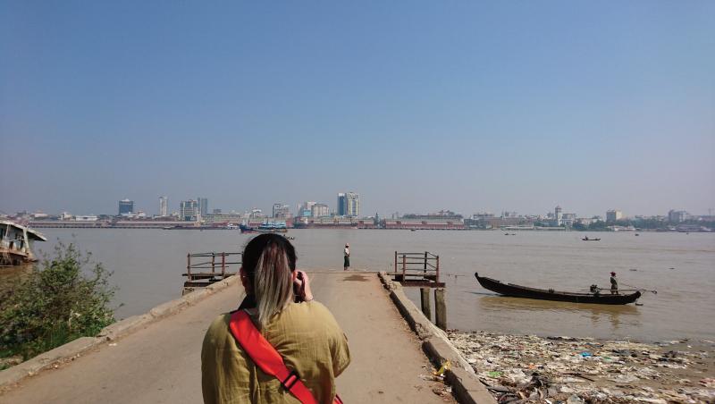 河的那岸高樓拔地而起;河的這岸有人舀起橘紅色溪水開始做飯