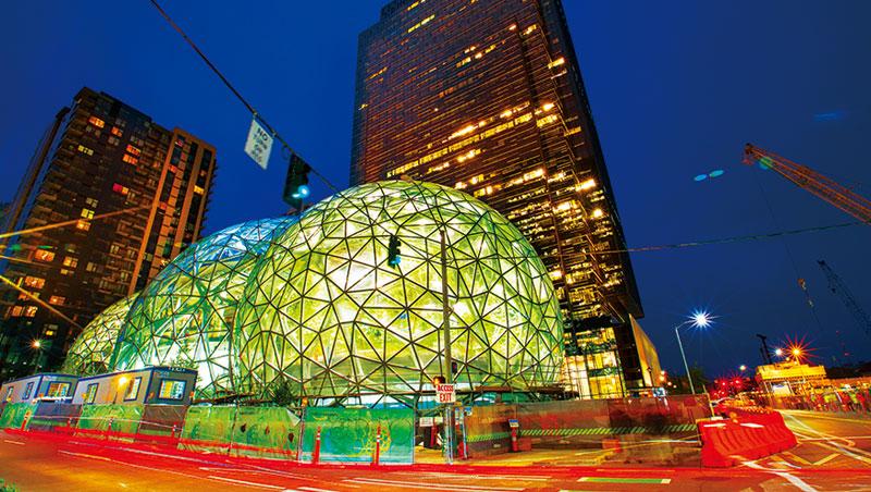 透明玻璃球與後方新落成的大樓,是新企業總部,也是創辦人貝佐斯辦公室所在。除了數百名資料科學家,更找來高達150 名經濟學家,以演算法來掌握消費者行為。