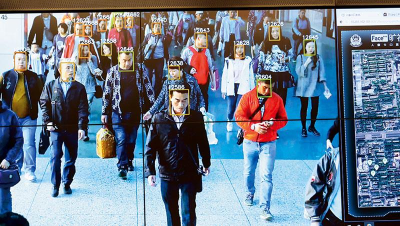 曠視牆上的螢幕播放用於杭州車站的安防系統,系統為每張臉生成一組編號,跟罪犯照片比對。
