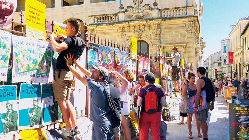 人群擠爆亞維儂老城區大街小巷,人人動手動腳,忙碌的吊掛藝術節演出的宣傳海報。