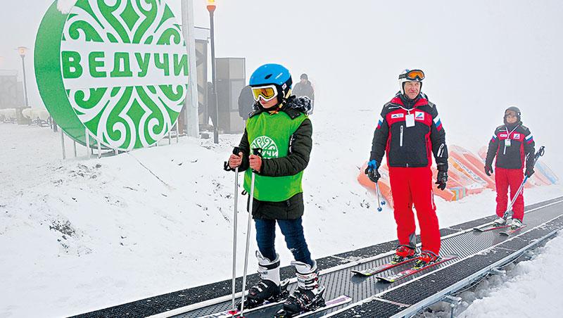 位於車臣的韋杜奇滑雪度假村開幕當天,運動選手站在雪橇上,搭乘地毯式升降梯爬上滑雪坡道頂端。