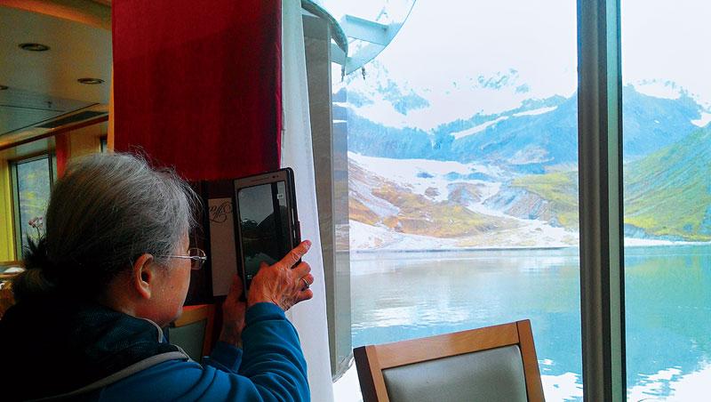 郵輪行經阿拉斯加冰河灣國家公園,媽媽吳素珠興奮拿出手機拍攝美景。陳美筑連忙幫媽媽上傳臉書打卡,紀念此刻。
