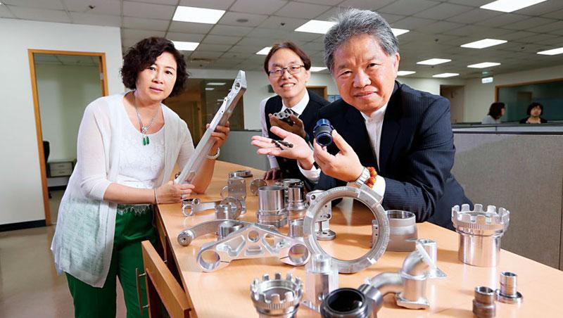 黃亞興(右)靠汽車零組件起家,但航太事業也是今年營收成長一大引擎,他左手上的正是近年新研發、代工的波音787飛航系統零件。