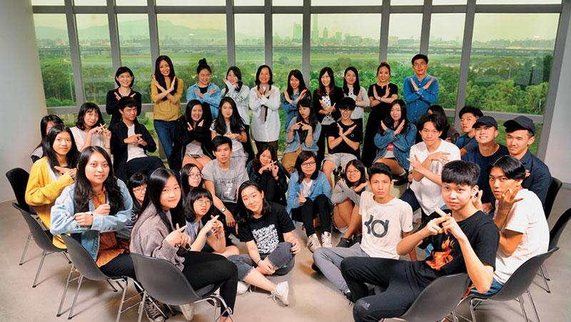 學學實驗教育機構創辦人徐莉玲(最後排左5),帶學生用手勢比出學校Logo,也象徵著跟過去傳統教育說NO。