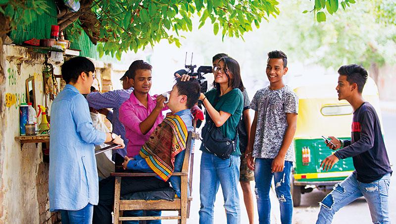 我剪髮時,攝影師陳兆瑜邊拍攝,騎車的印度年輕人馬上停下車跑來參觀:外國人怎麼在樹下剪頭髮?