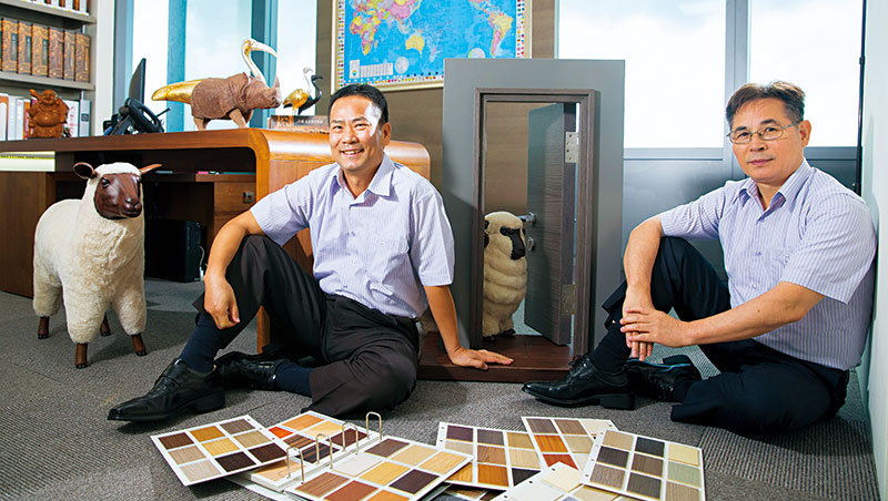 曹憲章(左)與黃天化(右)這對裝潢工出身的企業家,最新布局是將木皮板技術延伸到家具製作,實際成品有他們身旁的木桌、鋼刷實木門樣品與木綿羊裝飾品等。