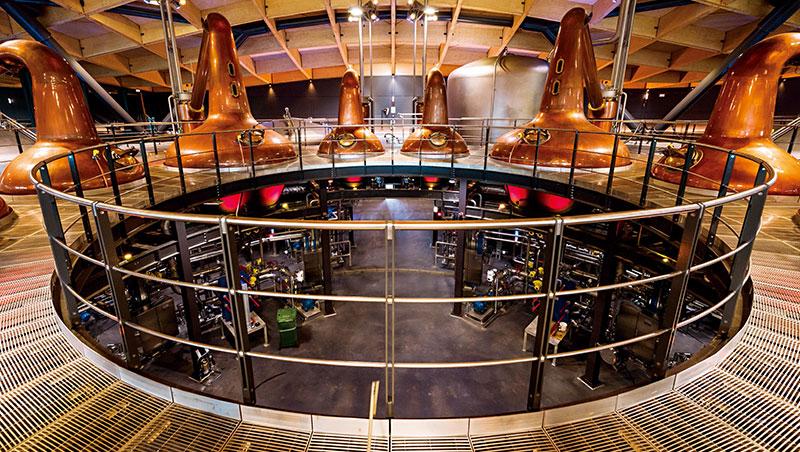 罐式蒸餾器、發酵槽和烈酒蒐集槽以奇異的圓周形式呈現,與下方高科技管路和設備相映成趣。