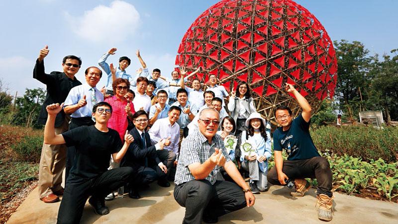 5層樓高的機械花,光傘面的紅色,就經2個月反覆試驗選定。豪華朗機工核心成員張耿華(右1)與合影大老闆、製作團隊笑稱,這顏色是特製的「花博紅」。