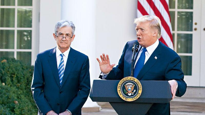 去年獲川普(右)任命的聯準會主席鮑爾(左),因堅持繼續升息,引發股市動盪,遭川普揚言要開除。