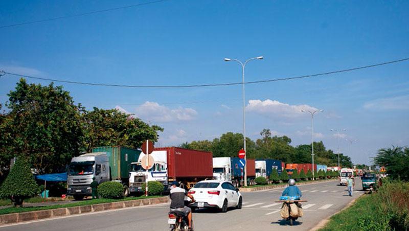 在柬越邊境機構前,貨櫃車潮等待通關,以曼哈頓經濟特區來說,每月進出口的40呎貨櫃就有1,200個。