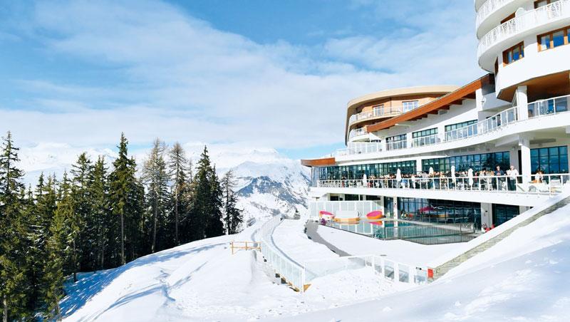 呈流線型外觀設計的度假村沿雪坡興建,旅客在露台欣賞環繞雪景。