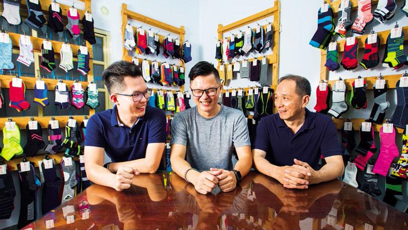 葉仕興(左)與葉仕平(中)成功讓中和製襪翻身,雖然爸爸葉東成說:「表現還可以啦!」但眼裡卻難掩驕傲。