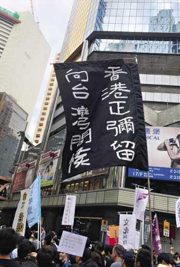 遊行中,一位只會講粵語的中年男子舉著旗幟,要台灣人堅持民主體制。