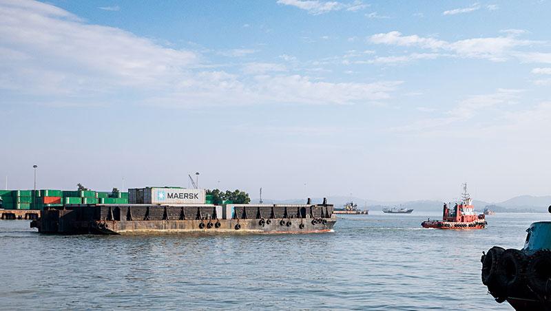 巴淡沒有深水港,貨櫃得先放在駁船(左)由拖船(右)拉到20公里外的新加坡,換上大型貨輪後,才能前進最終目的地。