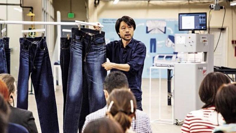 JIC首席營運總監松原正明,向來自17國的媒體解釋迅銷牛仔褲新製程,他手中的牛仔褲刷色,正是雷射雕刻機製造的效果。